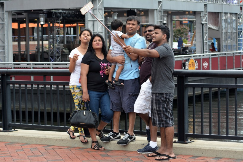 A guy doing a family selfie downtown Baltimore. Photo by Mike Hartley